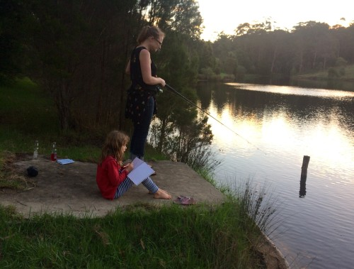 Lauren fishing and Charlize recording the day's events in her new journal.